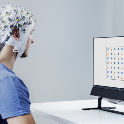 A young man wearing eeg cap in front of tobii pro